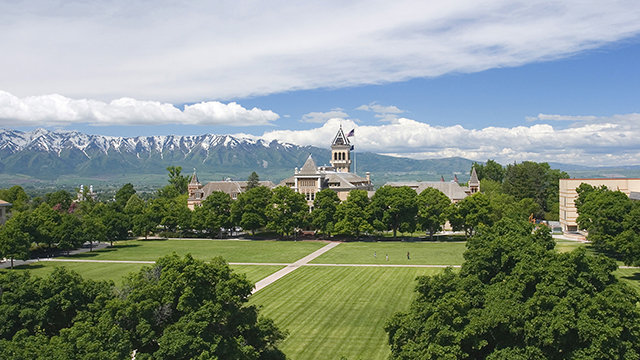 View of USU's Old Main building with the Wellsville mountains in the background.